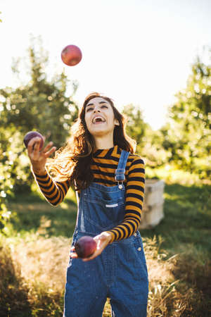 Young woman, in rural environment, juggling with apples LANG_EVOIMAGES