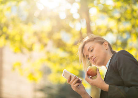 Young city businesswoman reading smartphone text and eating apple
