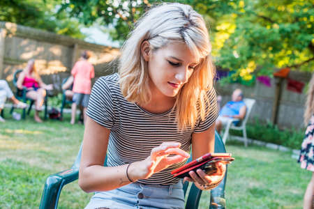 Young woman texting on smartphone at party in garden