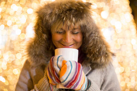 Mature woman wearing furry hood and mittens holding hot drink in front of xmas lights LANG_EVOIMAGES