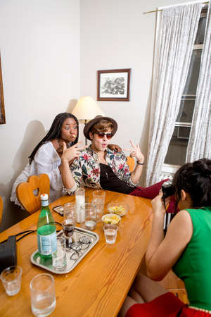 housing lot: Young hipster couple in posing for instant photograph at table