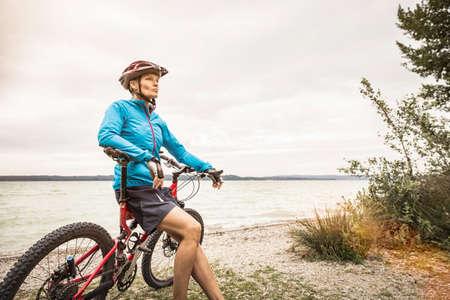Mature female mountain biker leaning against mountain bike at lakeside