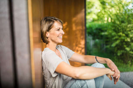 Portrait of mature woman sitting relaxing outside house LANG_EVOIMAGES