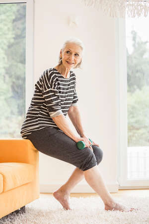 Senior woman sitting on sofa with dumbbell LANG_EVOIMAGES