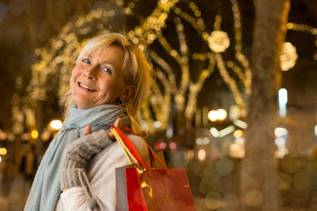 Portrait of mature woman with xmas shopping on tree lined avenue, Majorca, Spain
