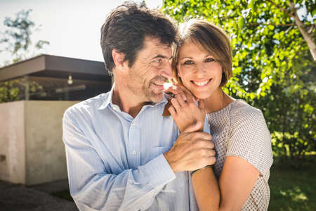 Portrait of mature couple outside new house LANG_EVOIMAGES