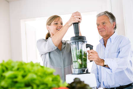 Couple preparing vegetable smoothie in kitchen LANG_EVOIMAGES