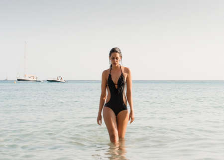 sultry: Young woman wearing bathing costume paddling in sea