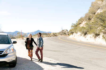 Young couple by car on mountain road smiling, Chilao Campgrounds, Los Angeles, California, USA LANG_EVOIMAGES
