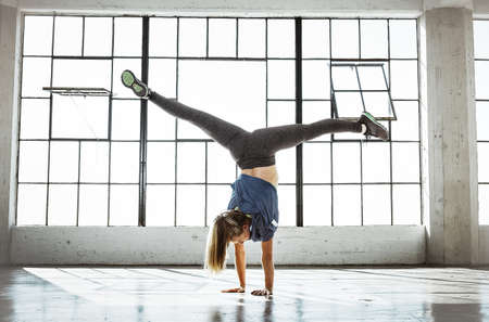 Rear view of young woman in gym doing handstand, open legs LANG_EVOIMAGES