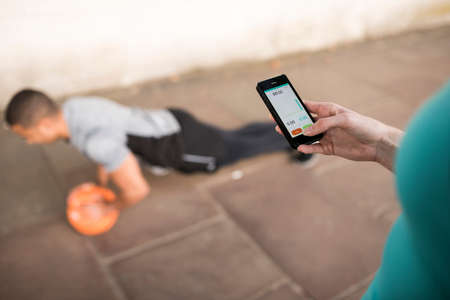 athletic wear: Over shoulder view of female trainer timing male runners push ups on smartphone