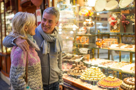 Romantic mature couple at cake shop window, Majorca, Spain LANG_EVOIMAGES