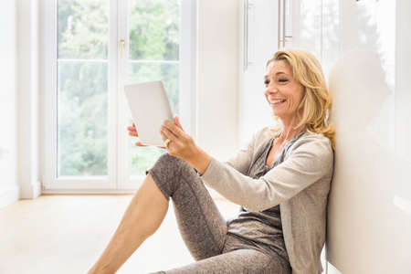 Mature woman sitting on floor at home reading digital tablet LANG_EVOIMAGES