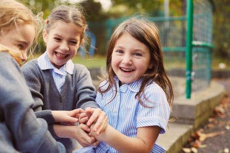 Elementary schoolgirls playing hand game in school playground