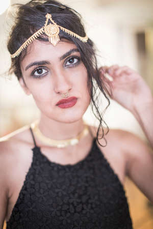 Portrait of beautiful young woman wearing gold headdress LANG_EVOIMAGES