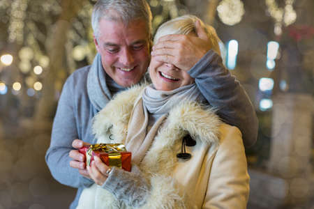 54: Mature man handing with xmas gift to wife on tree lined avenue, Majorca, Spain