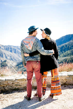 embraced: Full length rear view of young couple in mountains wearing hats face to face, Chilao Campgrounds, Los Angeles, California, USA