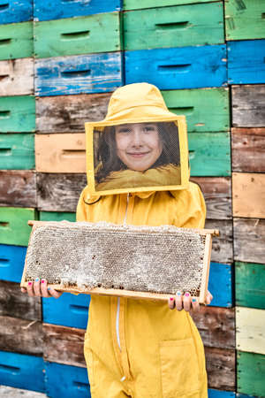 Young girl wearing beekeper dress holding hive frame