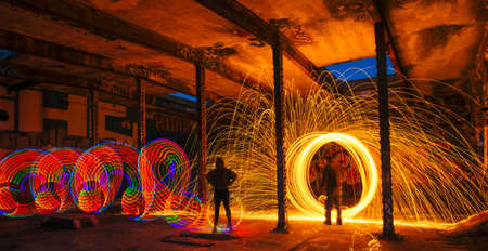 Man and woman creating multi-color and golden spark light trails in derelict building
