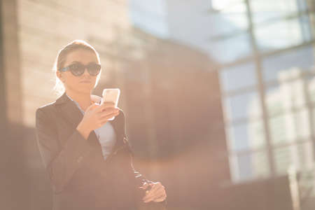 english ethnicity: Young city businesswoman reading smartphone text outside office
