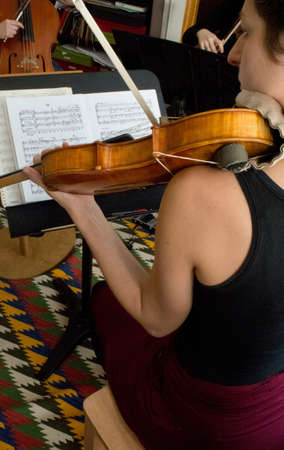 musical score: Young women playing violin in string quartet practice, rear view LANG_EVOIMAGES