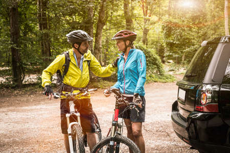 Mature mountain biking couple chatting in forest car park
