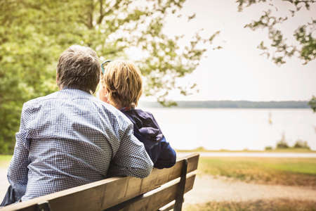 Rear view of adult couple on lakeside park bench