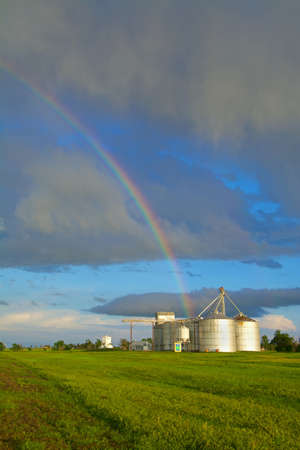 Rainbow over grain silos and lush green grass, Knowles, Oklahoma, USA