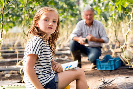 relaciones laborales: Girl sitting drawing while grandfather works looking at camera LANG_EVOIMAGES