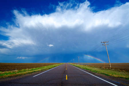 environmental issues: A highway leads to a storm and a rainbow west of Healy, Kansas, USA