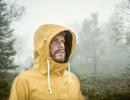 Bearded young man in misty forest wearing hooded yellow raincoat looking away LANG_EVOIMAGES
