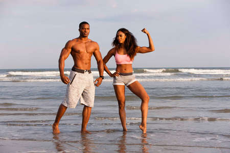 Couple on beach, flexing muscles, posing