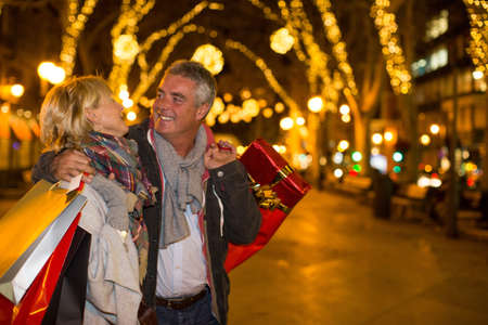 shopping buddies: Mature couple carrying xmas shopping on tree lined avenue, Majorca, Spain