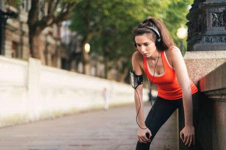 armbands: Female runner wearing headphones taking a break on riverside LANG_EVOIMAGES