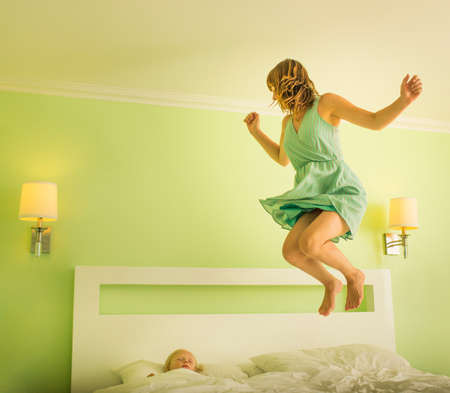 Mother jumping on bed to wake sleeping son