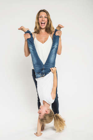 Studio portrait of mid adult woman holding daughter upside down LANG_EVOIMAGES