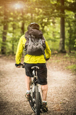 Rear view of mature male mountain biker cycling in forest