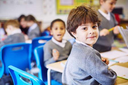 Portrait of boy looking over his shoulder in elementary school classroom