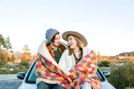 getting out: Young couple on car bonnet wrapped in patchwork blanket face to face smiling, Chilao Campgrounds, Los Angeles, California, USA