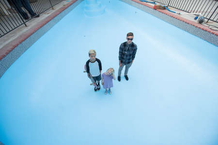 High angle view of siblings standing in empty swimming pool looking up at camera