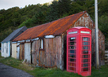 Traditional red public phone booth against rusted dilapidated corrugated iron building, Highland, Scotland