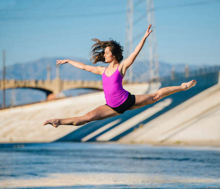 Dancer in mid air, arms raised doing the splits, Los Angeles, California, USA LANG_EVOIMAGES