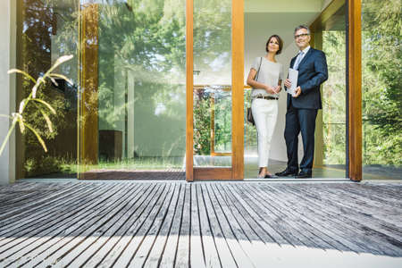 Mature woman looking at new house patio with estate agent