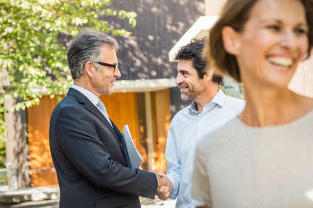 sold small: Estate agent and mature man shaking hands outside new house LANG_EVOIMAGES
