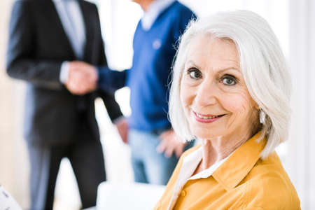 Senior woman in business meeting looking over shoulder at camera smiling