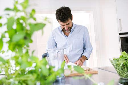 produits alimentaires: Homme d'âge mûr coupant du gingembre au comptoir de la cuisine