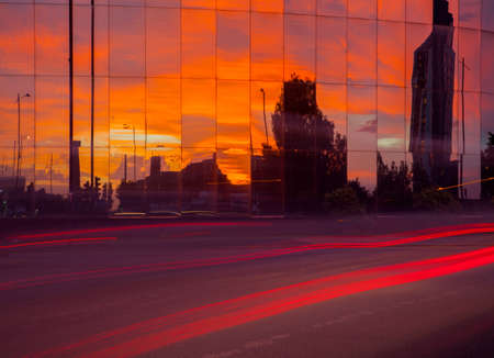 Highway traffic light trails and glass fronted office building at sunset