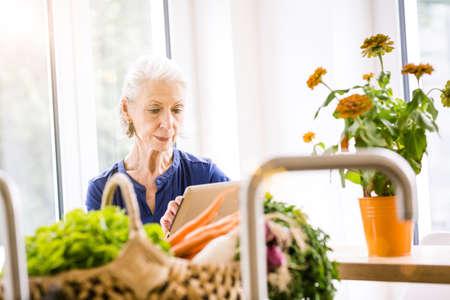 silver screen: Senior woman browsing digital tablet at kitchen counter