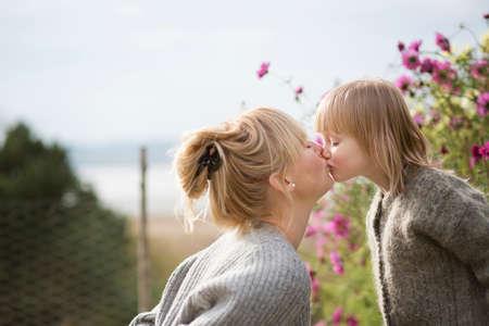 Mother kissing son in organic garden