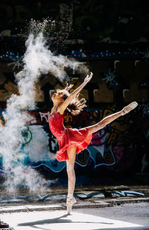 Ballet dancing girl scattering white powder in front of graffiti LANG_EVOIMAGES